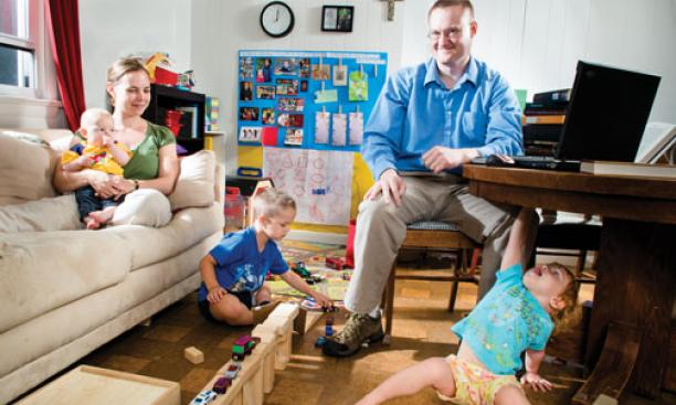 Dan Johnson GS; his wife, Julie; and their children Anders (5), Lucia (2), and Henrik (5 months) make good use of their small living room.
