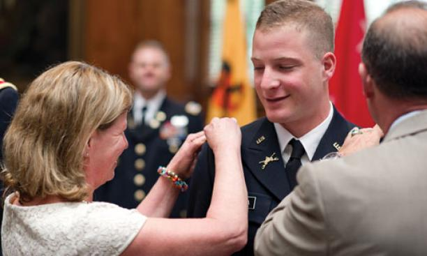 The parents of Greg Colella '12 proudly pin epaulettes on the uniform of their son, a second lieutenant.