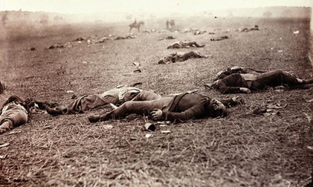 "A Harvest of Death: Taken at Gettysburg on a ""sunless morn"" following the great battle, this photo elicited Gardner's sermonizing: ""Such a picture conveys a useful moral,"" he wrote. ""It shows the blank horror and reality of war, as opposed to"