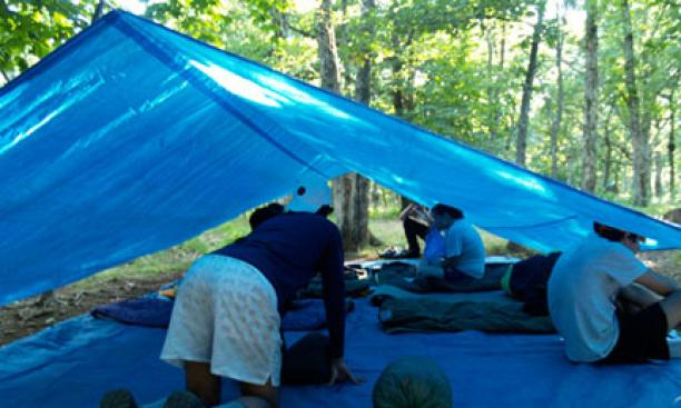 Setting up camp under a tarp for the night.