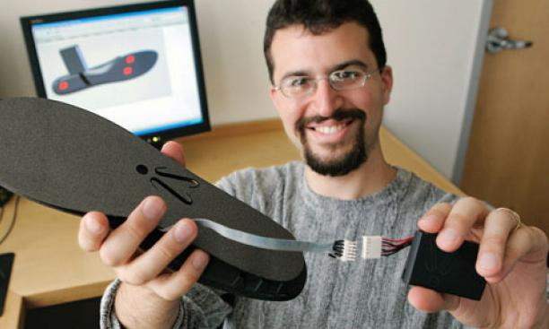 In this 2008 photo, Aiden displays the shoe insole he developed to detect when a wearer is losing balance.