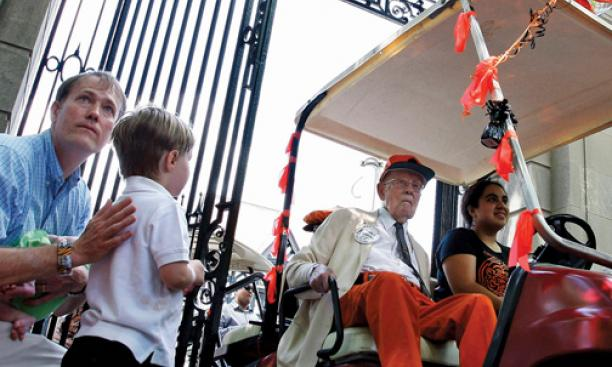 Riding in his golf cart at the P-rade in 2011, Warnock passes PAW writer W. Barksdale Maynard '88 and his son, Alexander.