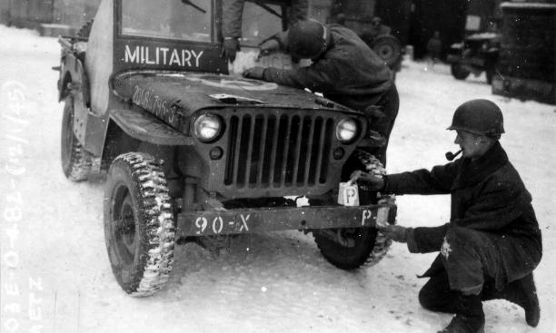 The Ghost Army also took care to make its markings consistent with the unit it was impersonating. In Metz, France, soldiers stencil 90th Division markings on the bumper of a jeep.