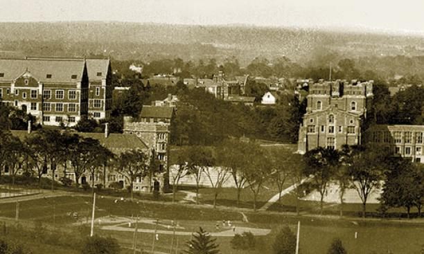 Large science labs Palmer and Guyot are pictured with the rooftops of Prospect Avenue clubs between them. A ballgame is underway at Brokaw Field, today the site of Whitman College. Stately trees on Elm Drive screen Patton dormitory, with tennis courts on