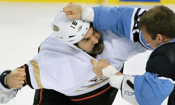 George Parros '03, left, who plays right wing for the NHL's Anaheim Ducks, brawls with a Florida Panthers player in February.