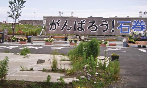 "A brightly painted sign in a heavily damaged area reads, ""Let's do our best – we can do it, Ishinomaki!"""