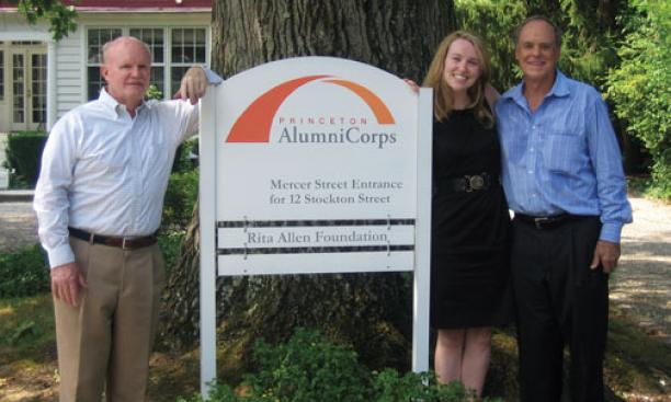 Standing next to the sign introducing Princeton AlumniCorps — formerly Princeton Project 55 — are, from left, president Bill Leahy '66, executive director Kathleen Reilly, and board chairman Kenly Webster '55.