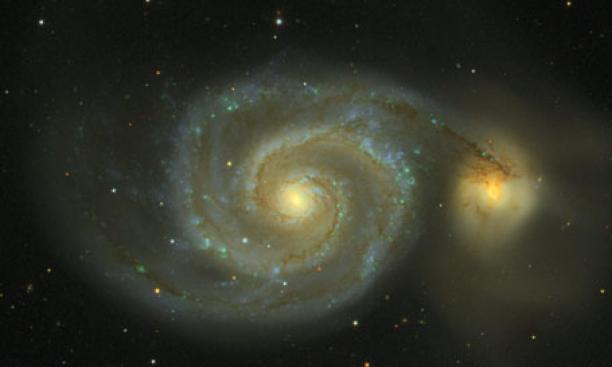 Messier 51, as observed in the Sloan Digital Sky Survey, is actually two galaxies in collision. The impact, which will take 100 million years to complete, creates the spiral arms and the spray of stars visible at the right. Known as the Whirlpool Galaxy,
