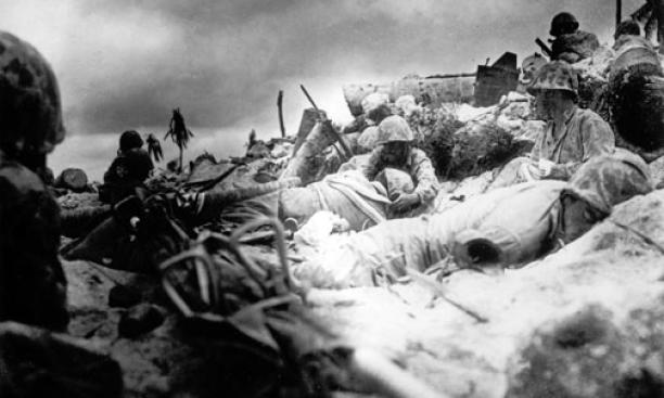 Marines, many of them wounded, take cover behind a sea wall on Red Beach No. 3 during the initial landing at Tarawa Nov. 20, 1943.