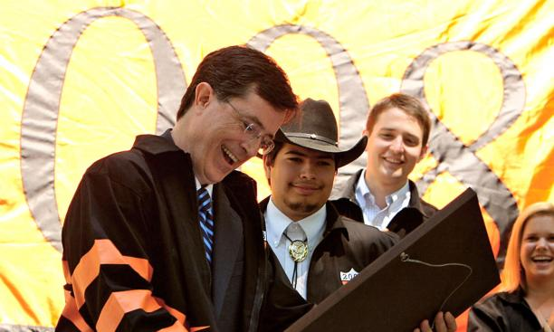 "Stephen Colbert, left, receives an ""Understandable Vanity Award"" from seniors including Class Day co-chairman Jonathan Galeano (from Texas) and class president Tom Haine."