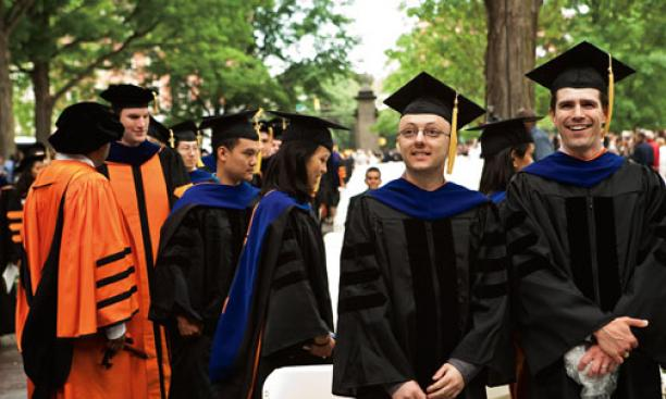 Alexandros A. Ntelekos *08, foreground, left, whose degree was awarded in September; and Spencer E. Quiel *09 watch the proceedings as other Ph.D. recipients file in behind them. Both men were in the Department of Civil and Environmental Engineering.