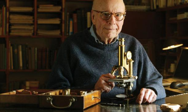 Professor emeritus John Bonner in his office in Guyot Hall with Conklin's microscope.