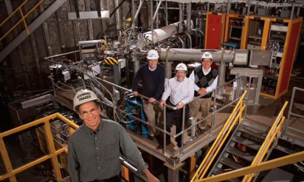 Stewart Prager, foreground, and from left, Richard Hawryluk, Robert Goldston *77, and Masayuki Ono *78 stand in front of the NSTX fusion machine, which is hidden by hardware.