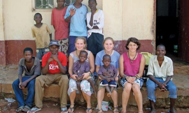 Annie Sprogell, wearing blue T-shirt, who is taking a gap year before entering Princeton, sits outside her house in Uganda with students and fellow teachers and gap-program participants.