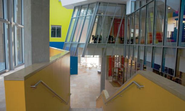 As seen from the front entrance, an atrium-passageway painted in brilliant colors divides the building in two. At right, the science library proper is visible behind its curtain wall of glass; at left are classrooms and offices.