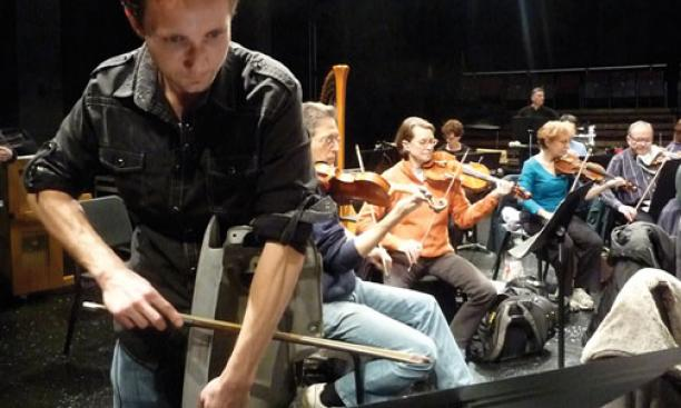 "Sean Friar GS bows a car fender during a rehearsal of his ""Clunker Concerto."""