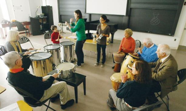 As part of Alumni Day activities, alumni and family members take part in a drum circle led by Frances Cornelius '10, standing left, and Janet Kim '10, members of Princeton's Modern Improvisational Music Appreciation group.