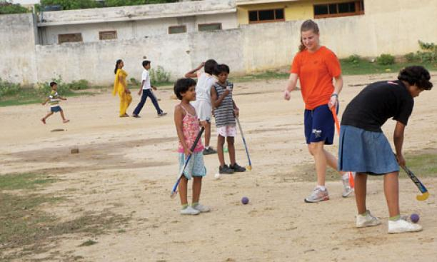 Allison Behringer '12, a varsity field hockey player, introduced the sport to children at an orphanage in India where she taught during her summer 2010 internship. Below, Alex Banfich '12 with French pupils at a July 4th celebration.
