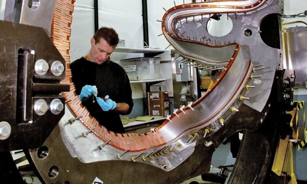 PPPL technician Doug Voorhees works on one of the stellerator's 18 coils. The project is being shut down.
