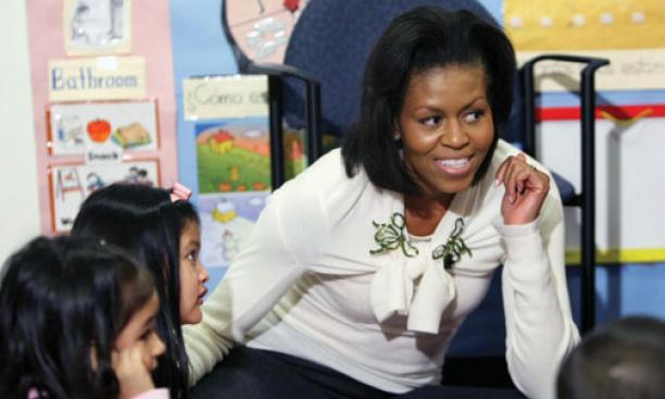 First lady Michelle Obama '85 listens to children at Mary's Center, a community social-service center, in Washington in February.
