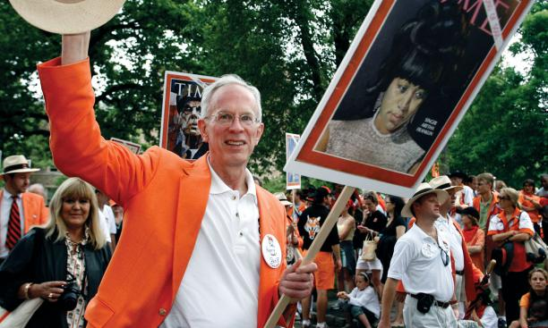 "Henry ""Hank"" Bone '68 tips his hat to onlookers along the P-rade route."