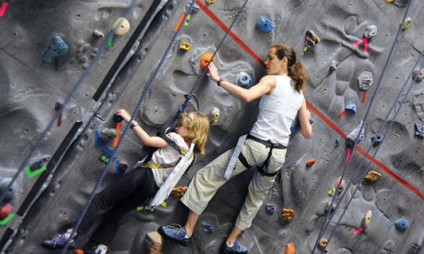 Eleanor Harrison '92 and daughter Isabelle Harrison Bregman scale the indoor climbing wall at Princeton Stadium