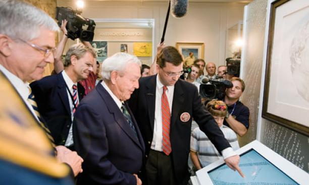"Rand Jerris *99, center, shows an interactive display of the portrait ""Gratitude"" to Arnold Palmer at the USGA Museum's reopening in June 2008."