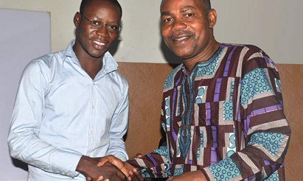 Leonard Wantchekon, right, congratulates Romaric Samson on earning a master's degree from the institute in Benin, West Africa, that Wantchekon founded.