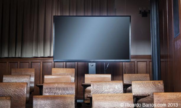 LARGE MONITOR: A movable, 70-inch screen can be set up in the back of the room that allows the lecturer at the podium to see and address both the McCosh audience and those ­conferencing in from another location at the same time. The ­monitor also can fu