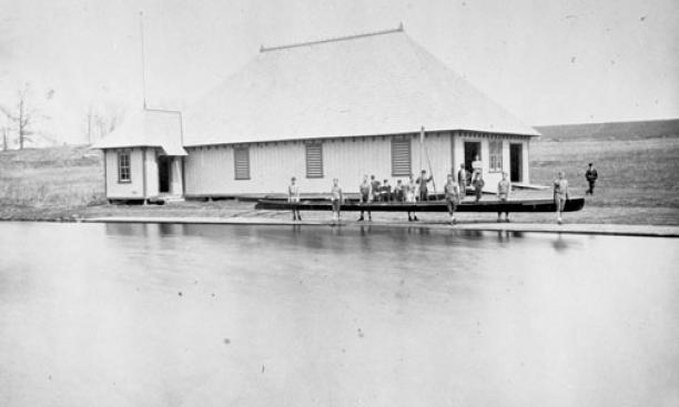Crew members prepare for practice in front of the original campus boathouse in 1875