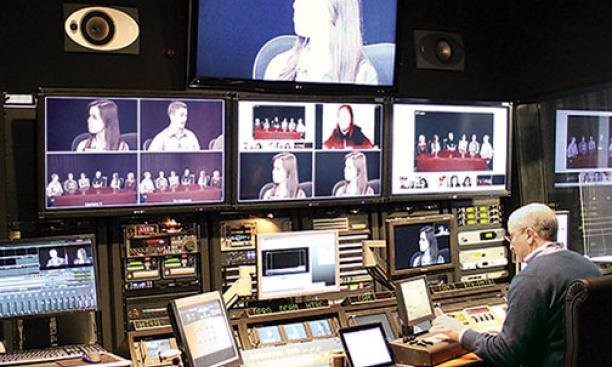Students in an online course taught by Professor Jeremy Adelman are shown on screens at Princeton's Broadcast Center as broadcast engineer Dan Kearns operates the console.