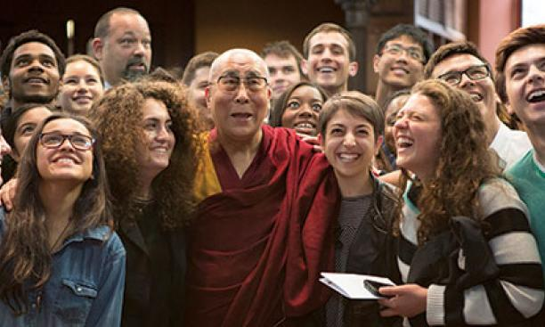 Students look up for a photo with the Dalai Lama in Chancellor Green.