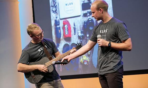 Adam Klosowiak '15, left, demonstrates a KLOS travel guitar with Jake Sheffield, also of KLOS.