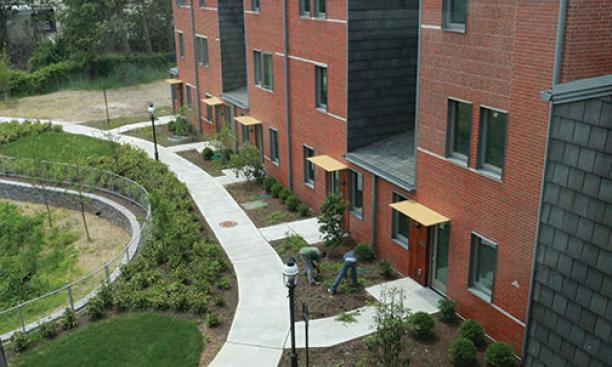 A curving walkway connects townhouse units.