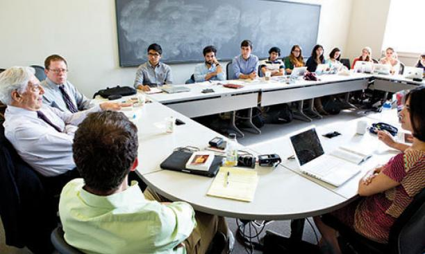 Students listen to Peruvian author Mario Vargas Llosa, left, during a seminar on his writings.