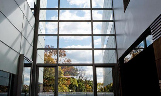 The view south from the two-story atrium of the neuroscience/psychology building; an outdoor patio is beyond the glass wall.