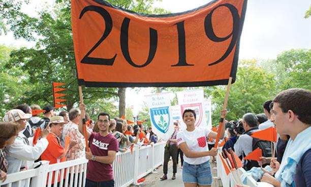 Josh Faires '19 and Victoria Davidjohn '19 carry the banner for the Pre-rade as the class is welcomed by other students and alumni.