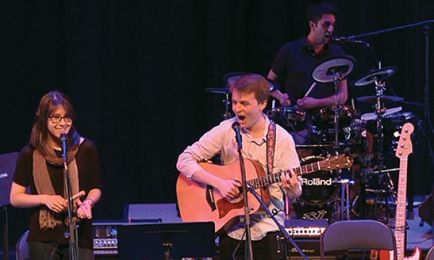 "Performing ""Death by Mall"" during a concert by student songwriters are, from left, Sydney King '17, Charlie Baker '17, and Arjun Dube '15 on drums."