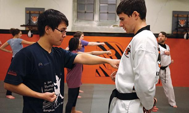 Joe Rummanthorn '18, left, learns to aim a punch from taekwondo instructor Matthew Weinberg, a postdoc.