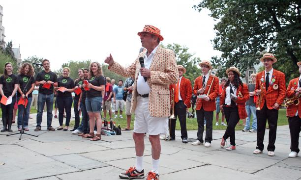 Tom Meeker '56, a longtime class secretary and lover of all things orange and black, teaches the new class the locomotive cheer.