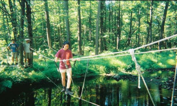 Traversing a three-rope bridge at Princeton Blairstown Center.