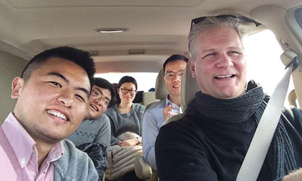 "Frank Langfitt '86 with his NPR assistant, Yang Zhuo (left), and passengers in the ""Free Loving-Heart Taxi"""