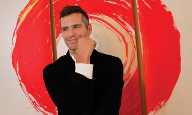Miller in front of an illustration at the Zen Hospice Project.