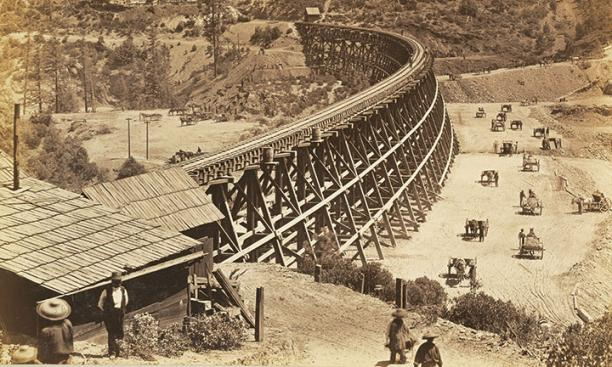 Chinese workers fill in a ravine alongside a large trestle for the Transcontinental Railroad in this photo, taken in 1867.