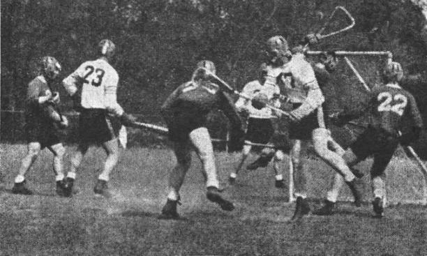 Rutgers goalie Don Gucker leaps to stop a shot by Bob Russell '55.
