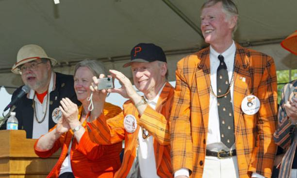 In the P-rade reviewing stand are, from left, announcer Gregg Lange '70; President Tilghman; Stephen Oxman '67, chairman of the executive committee of the trustees; and David Siegfried '64, president of the Alumni Association.