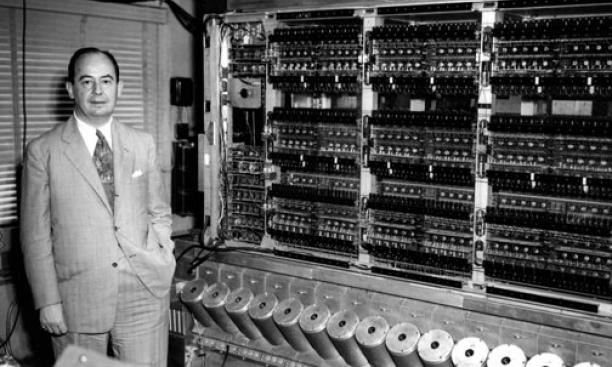 John von Neumann with MANIAC in 1952. The shiny cylinders contained random-access memory, visible as flickering phosphor through the holes.