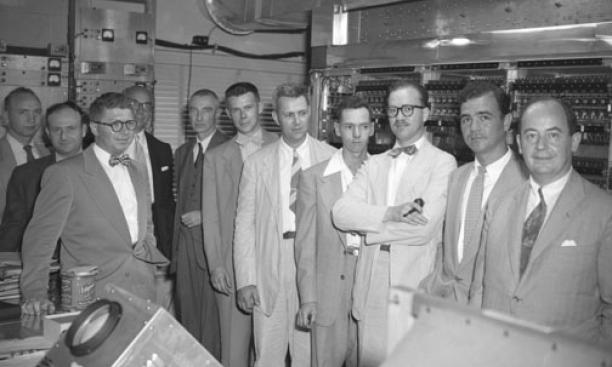 With MANIAC on dedication day in 1952 were Gerald Estrin (third from left), atomic physicist Robert Oppenheimer (fifth from left), and von Neumann (far right).
