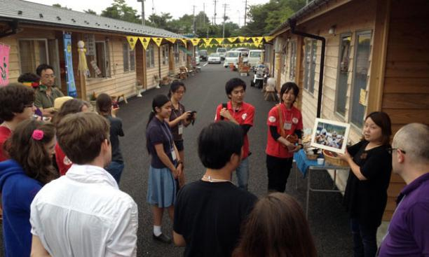 Students listen to a shopkeeper at a small shopping area in Onagawa created out of shipping containers.