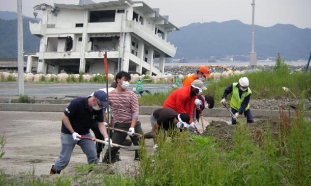 Participants in a Global Seminar studying issues facing post-tsunami Japan work to clear an area near a site in Kamaishi where dozens of homes were washed away.